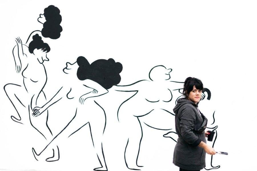 """Flavita Banana (Flavia Álvarez-Pedrosa), realizando el mural del 12+1 """"Juntes Sumem"""" en el Centre Cívic Cotxeres Borrell, Barcelona. Marzo de 2019."""