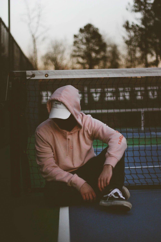 Hombre con hoodie rosa sentado en una cancha de tenis