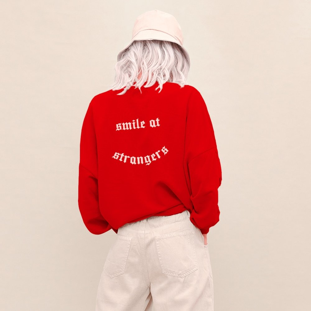 Mujer de espaldas con sudadera roja y letras blancas