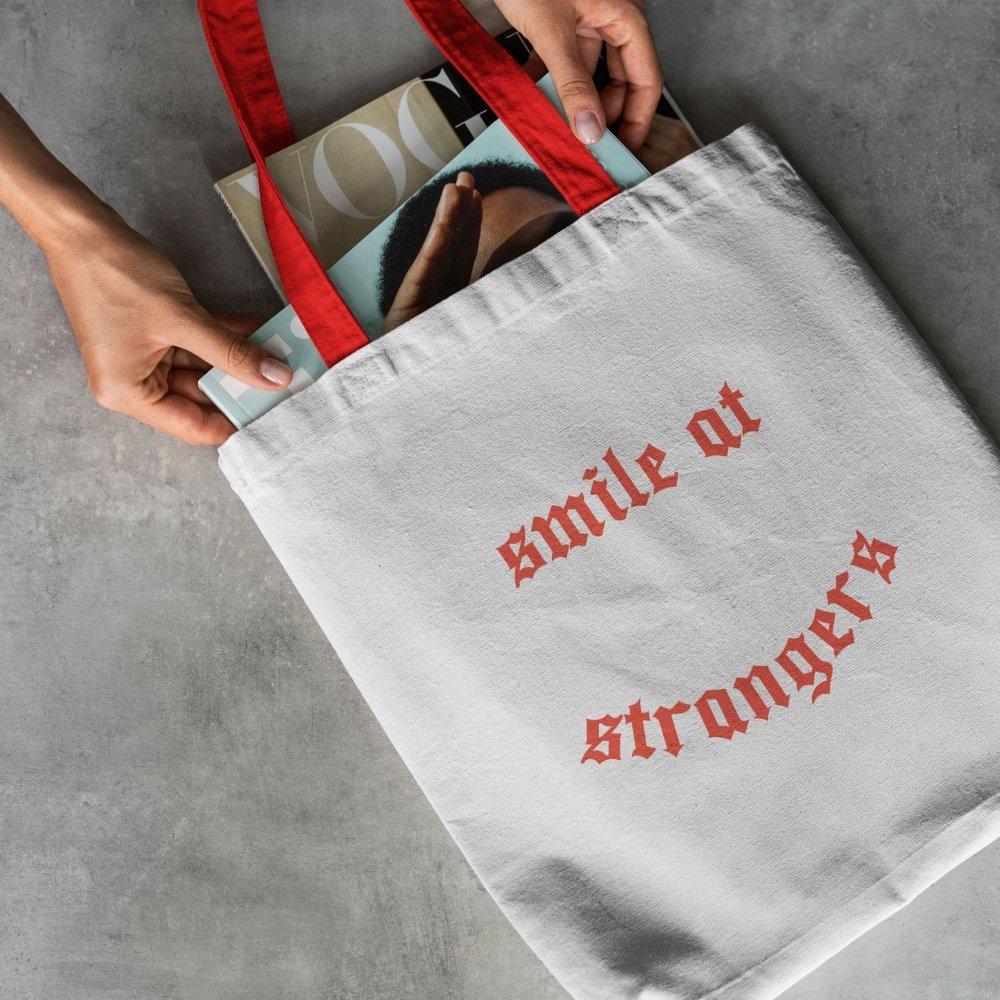 Manos sosteniendo revistas en una  Tote Bag blanca con letras y asas rojas
