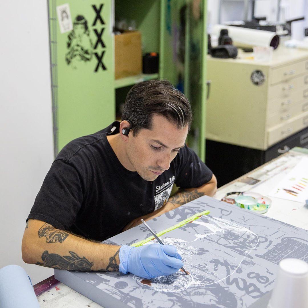 artista sostiene pincel con la mano y pinta una obra de arte