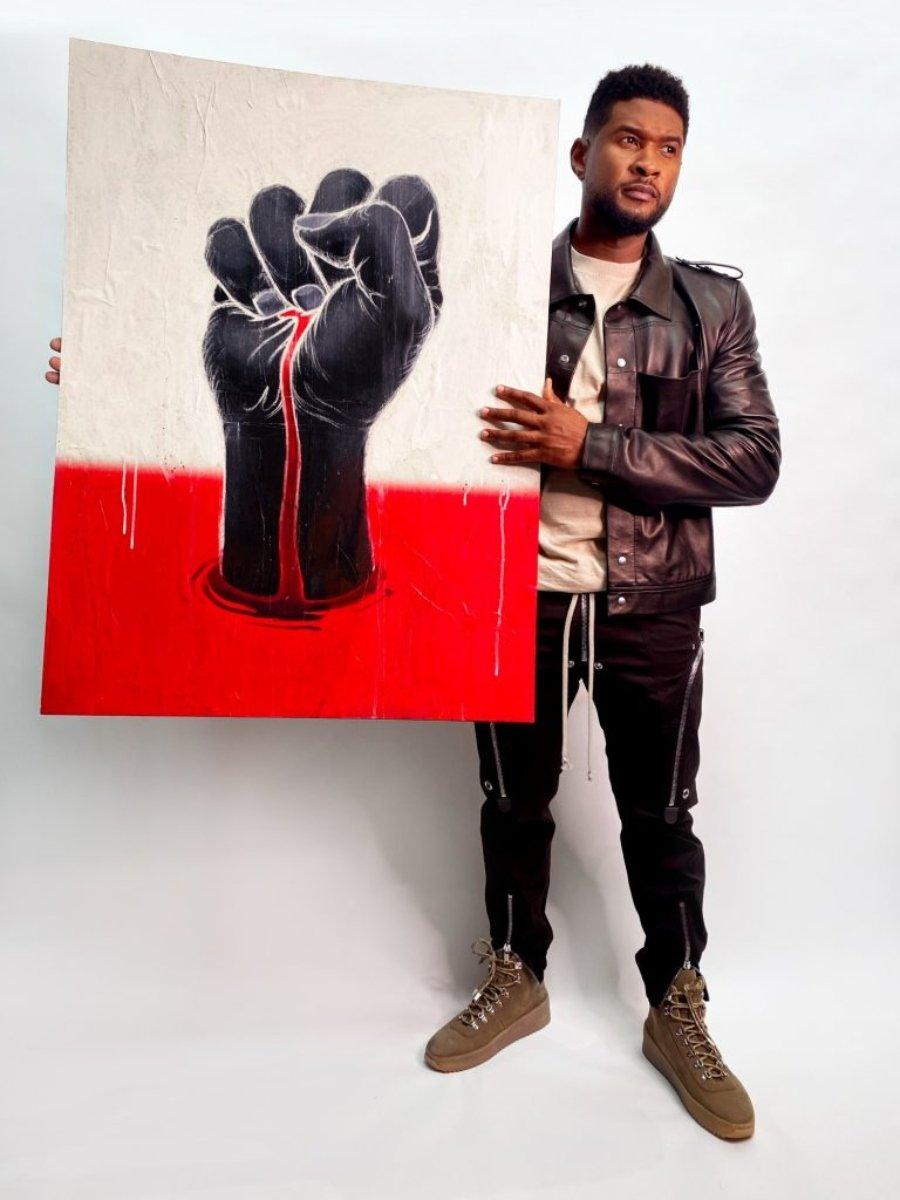 """Usher con su letrero y el de James Jean Can't Breath para la subasta """"Muéstrame los letreros"""". Foto cortesía del African American Policy Forum."""