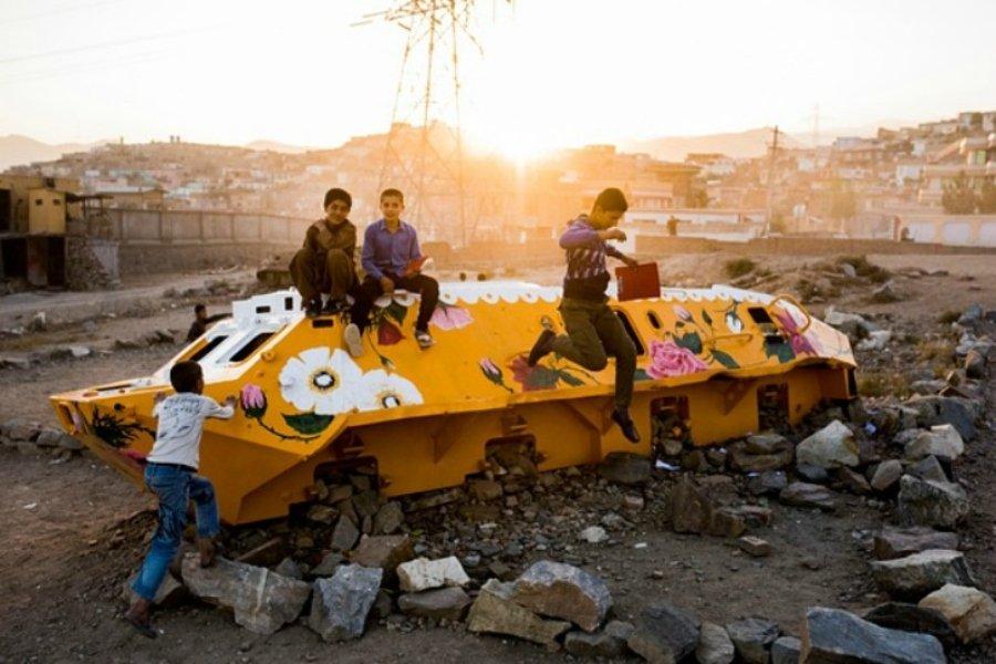 Niños jugando sobre tanque de guerra