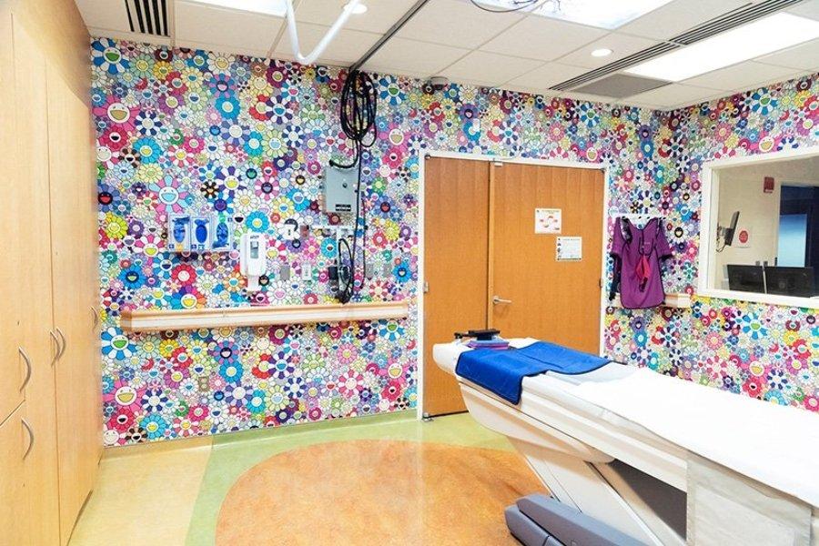 Cuarto de un hospital donde está la Cámara de tomografía decorada con flores de colores y nubes
