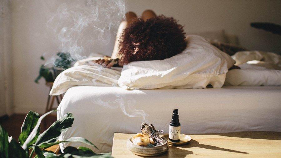 Mujer acostada sobre su cama junto a productos de CBD