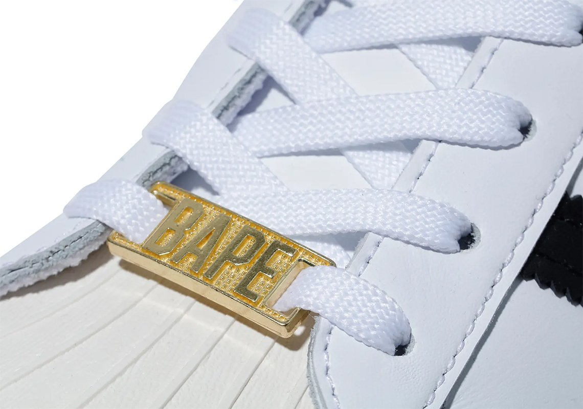 """PArte de unos tenis blancos con agujetas blancas y un brpche que dice """"BAPE"""" en dorado"""
