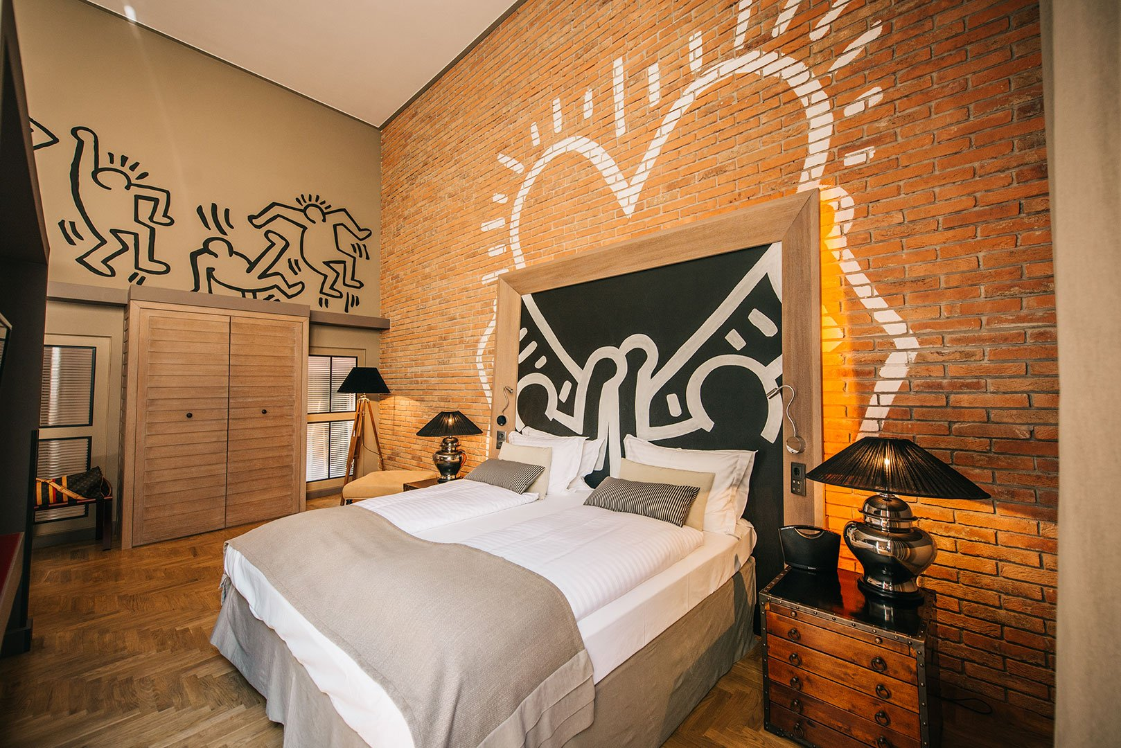 cuarto de hotel decorado con pinturas de Keith HAring
