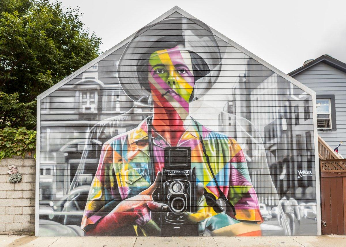 mural de un hombre con sombrero con camiseta de colores que sostiene una cámara análoga