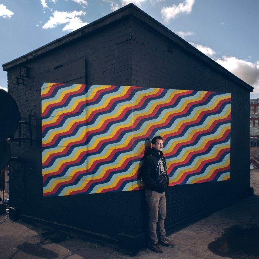 El artista posando frente a uno de sus murales